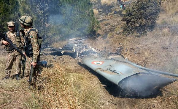 Pakistani soldiers stand next to what Pakistan says is the wreckage of an Indian fighter jet shot down in Pakistan-controlled Kashmir in the Bhimber district near the Line of Control on Wednesday.