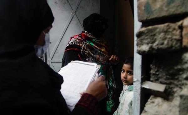 Polio vaccinator Zeenat Parveen, holding the clipboard, and a volunteer go door-to-door to reach children in Rawalpindi, a city near the Pakistani capital of Islamabad.