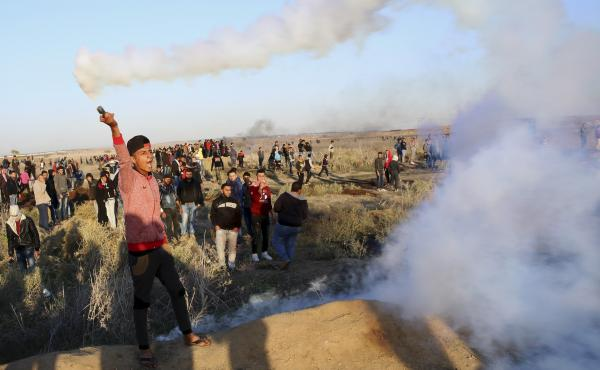 A Palestinian protester throws back a tear gas canister that was fired by Israeli soldiers during clashes on the Israeli border after a protest against President Trump's decision to recognize Jerusalem as the capital of Israel.