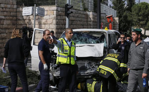 An Israeli police officer gestures in front of the vehicle of a Palestinian motorist who rammed into pedestrians in Jerusalem on Wednesday.