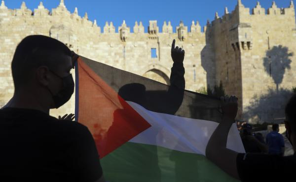 Demonstrators wave the Palestinian flag during a protest in Damascus Gate, just outside Jerusalem's Old City on June 19. Palestinians and Jewish settlers hurled stones, chairs and fireworks at each other in a tense Jerusalem neighborhood, where settler gr