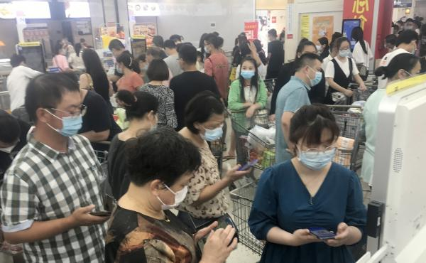 Shoppers turn out heavily Monday at a supermarket in Wuhan, China, after nearby residential blocks went into lockdown as part of COVID-19 prevention measures.