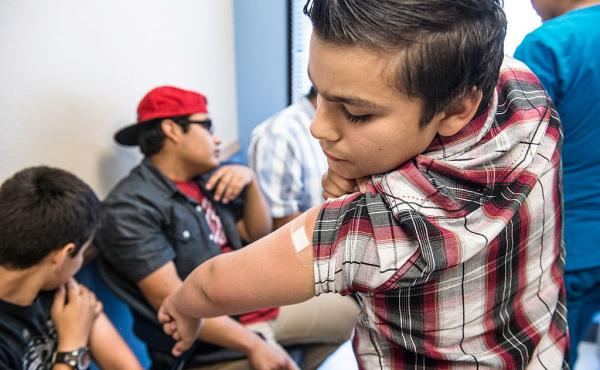 Abraham Vidaurre, 12, checks his arm after receiving an HPV shot in Corpus Christi, Texas. The vaccine is recommended for 11- and 12-year-old boys and girls.