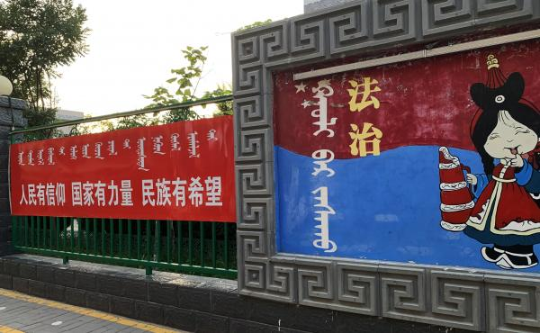 "A sign (left) outside a Mongolian-language school in Hohhot, Inner Mongolia, reads: ""When the people have conviction, the state has strength and the ethnic minorities have hope."" The sign at right says: ""Rule of law."""