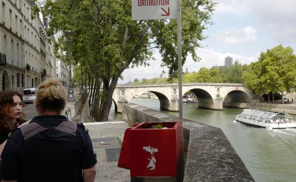 A municipal employee (right) talks to a pedestrian next to a controversial street urinal installed on the Seine river banks of Île de la Cité, Paris, in August.