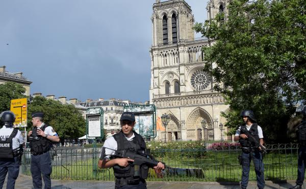 French police gather near the site of an attack near the entrance of Notre Dame Cathedral in Paris on Tuesday. Anti-terrorist prosecutors have opened an investigation after police shot and injured a man who had tried to attack officers with a hammer. One
