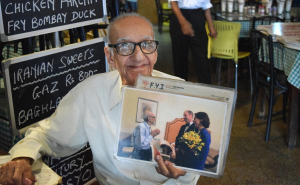Boman Kohinoor, 97, has spent the past eight decades committed to his beloved Britannia & Co., one of Mumbai's last Parsi cafes. Here, he proudly holds up a photo of himself with two members of the British royal family: the Duke and Duchess of Cambridge,