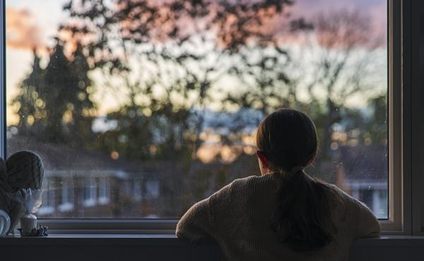 A girl looks out of her bedroom window as the sun is setting.