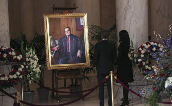 President Obama and first lady Michelle Obama look at a portrait of U.S. Supreme Court Justice Antonin Scalia after paying their respects in the Great Hall of the Supreme Court in Washington, D.C.