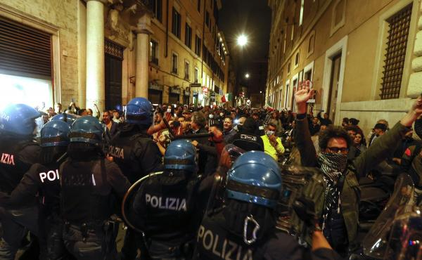 Anti-riot police officers face demonstrators trying to reach the Chigi Palace government office in Rome during a protest Saturday against green pass.