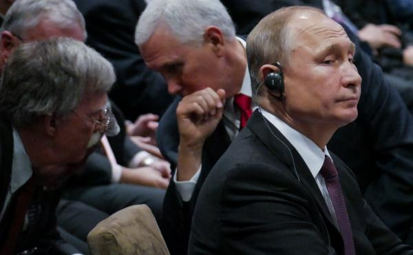 Russian President Vladimir Putin (right) sits beside Vice President Pence, who talks to U.S. national security adviser John Bolton (left) during the 13th East Asian Summit in Singapore on Thursday.