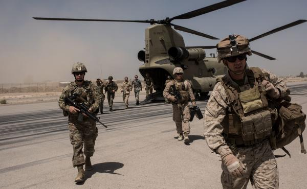 U.S. service members walk off a helicopter on the runway at Camp Bost in Helmand Province, Afghanistan on September 11, 2017.