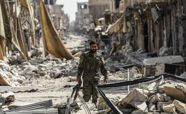 A member of the Syrian Democratic Forces, a group allied with the United States, walks through debris in Raqqa, Syria, formerly the de facto capital of Islamic State.