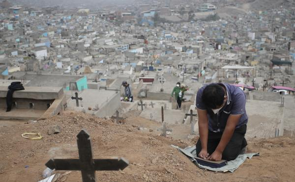 A relative prays at the Mártires 19 de Julio Cemetery on the outskirts of Lima, Peru, on Aug. 20. Peru has one of the world's highest per capita coronavirus-related death tolls, according to Johns Hopkins University.