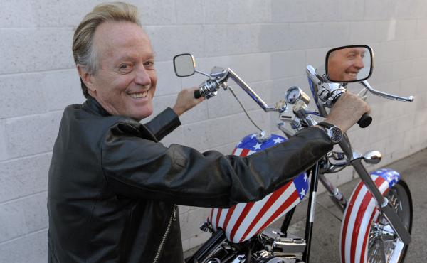 Peter Fonda poses in 2009 atop a Harley-Davidson motorcycle based on the one he rode in the 1969 film Easy Rider.