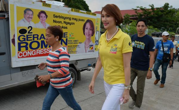 Geraldine Roman walks past a campaign poster during an April 30 trip to the town of Orani, in the province of Bataan, north of Manila. The 49-year-old, a member of a powerful political family, has won a seat in the nation's lower house, according to unoff