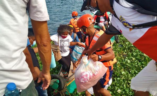 In this photo provided by the Philippine Coast Guard, families are evacuated by members of the Philippine Coast Guard to safer ground in Camarines Sur province as they prepare for typhoon Goni. Families living near coastal towns have moved to evacuation c