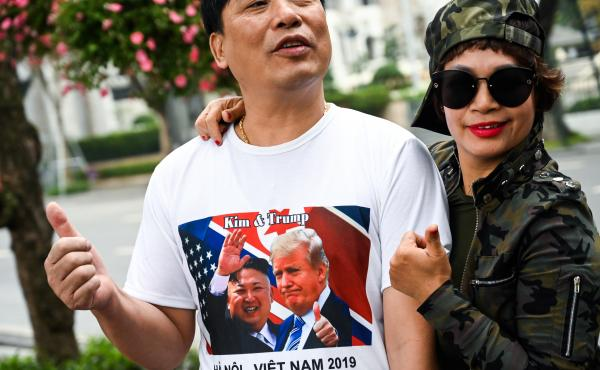 A man wearing a T-shirt featuring pictures of President Trump and North Korean leader Kim Jong Un poses near the Sofitel Legend Metropole hotel in Hanoi on Wednesday.