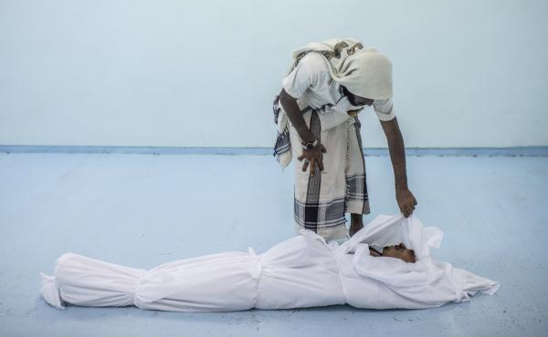 A friend attends to the body of a Yemeni fighter on Sept. 22.
