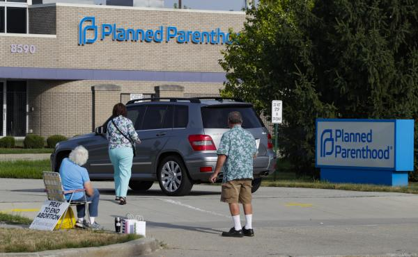 Abortion protesters attempt to hand out literature as they stand in the driveway of a Planned Parenthood clinic in Indianapolis on Aug. 16.