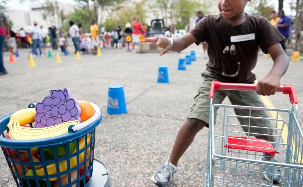 """A child runs a shopping cart relay during an Education Department summer enrichment event, """"Let's Read, Let's Move."""" The 2012 event was part of a summer initiative to engage youths in summer reading and physical activity, and provide them information abou"""