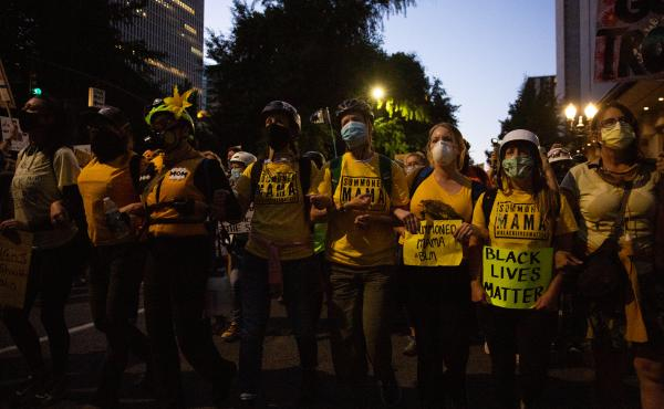 The Wall of Moms marches to the Multnomah County Justice Center in Portland, Ore., July 25, 2020. Portland has sustained protests against police brutality and systemic racism for 58 days.