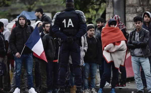 A French police officer oversees the evacuation of a makeshift camp in Paris on Tuesday. The camp, one of several set up by migrants and refugees around the French capital, held hundreds of people in degraded conditions for several weeks.