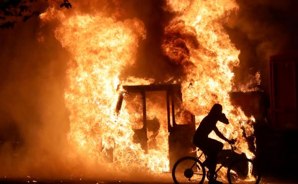 A man on a bike rides past a city truck on fire outside the Kenosha County Courthouse in Kenosha, Wis., during protests following the police shooting of Black man Jacob Blake on Sunday.
