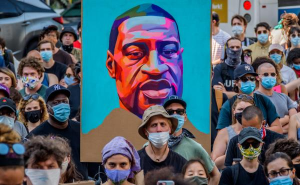 """Protesters hold a portrait of George Floyd at a demonstration against police brutality in New York City. Policing """"wasn't always this big. It wasn't always this bureaucratic,"""" journalist Jamiles Lartey says."""