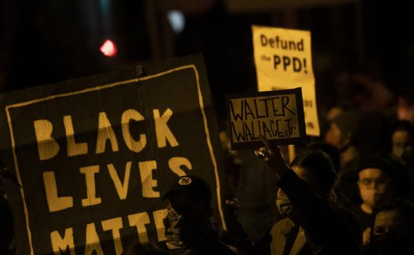 "Demonstrators hold placards reading ""BLACK LIVES MATTER,"" ""Walter Wallace JR."" and DEFUND PPD"" as they gather in protest near the location where Wallace, a 27-year-old Black man, was killed by two police officers in Philadelphia. Police officers said he w"