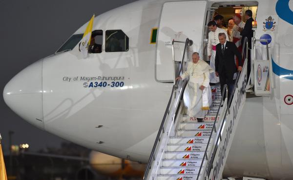 "Pope Francis disembarks from the plane upon his arrival at the airport in Manila, Philippines, on Wednesday. In comments to reporters aboard the plane, Francis said though the attack on Charlie Hebdo magazine was an ""aberration,"" free speech ""cannot make"