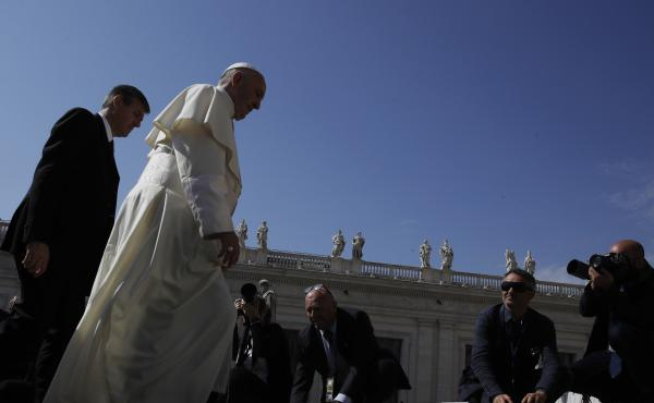 Pope Francis arrives in St. Peter's Square at the Vatican on Wednesday for his weekly general audience, the same day he tweeted his support for migrants and refugees.