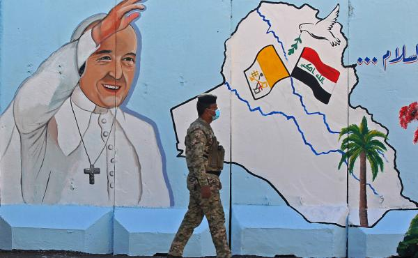 An Iraqi policeman walks by a mural depicting Pope Francis on the outer walls of Our Lady of Salvation Church in Baghdad on Monday. Pope Francis' visit from March 5 to 8 will include trips to Baghdad, the city of Mosul and a meeting with the country's top
