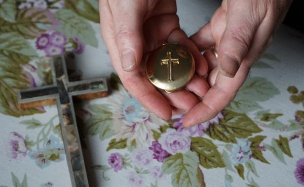 Marie Andrews holds a pyx, the vessel she uses to transport the consecrated Communion wafer to homebound parishioners. Andrews is an officially sanctioned Eucharistic minister in the Roman Catholic Church.