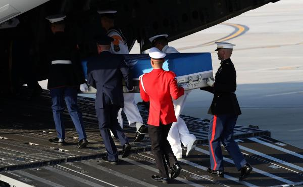 U.N. honor guards carry a casket containing remains transferred by North Korea onto a plane at Osan Air Base in Pyeongtaek, South Korea, on Wednesday. The remains will be analyzed in Hawaii to determine whether they are those of U.S. service members missi