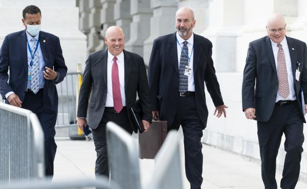 Postmaster General Louis DeJoy, second from left, leaves the U.S. Capitol after meeting Wednesday with Democratic leaders.
