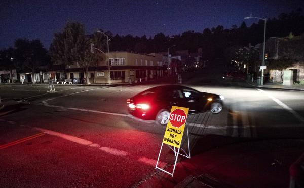 A car drives through a darkened Montclair Village during the power shutdown in Oakland, Calif., triggered by dry, windy weather.