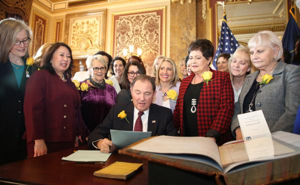 Utah Gov. Gary Herbert signs bill honoring the state's pioneering women suffragists on Wednesday. He's surrounded by state senators and representatives, and his wife, who are all wearing the yellow rose symbolizing suffrage.