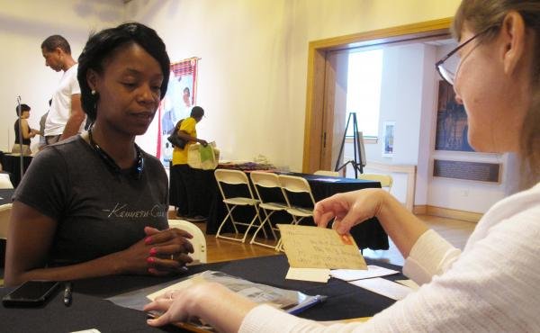 Neonta Williams (left) shares family letters dating back to 1901 with preservationist Kimberly Peach during the Smithsonian's Save our African American Treasures program at the Birmingham Civil Rights Institute. Peach advises her to use archive-quality po