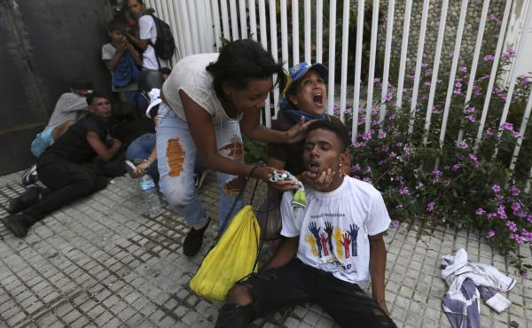 An anti-government protester calls for help as she and another woman help a fellow demonstrator who has been overcome by tear gas during clashes with security forces, in Caracas, Venezuela, on Wednesday.