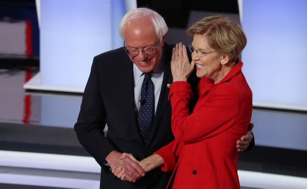 Sens. Bernie Sanders of Vermont and Elizabeth Warren of Massachusetts greet each other at the start of the Democratic presidential debate in Detroit in July.