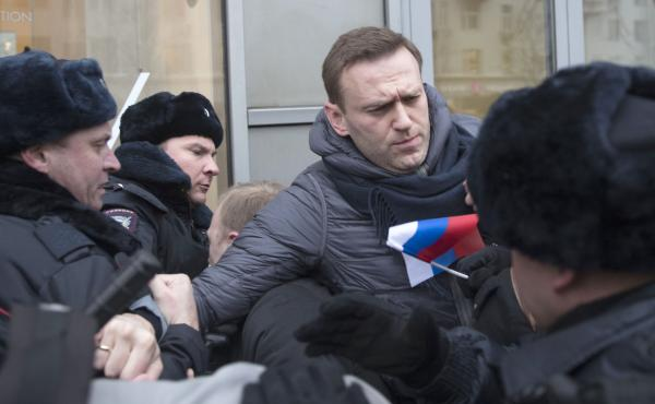 Russian opposition leader Alexei Navalny, center, is detained by police officers in Moscow, Russia on Sunday.