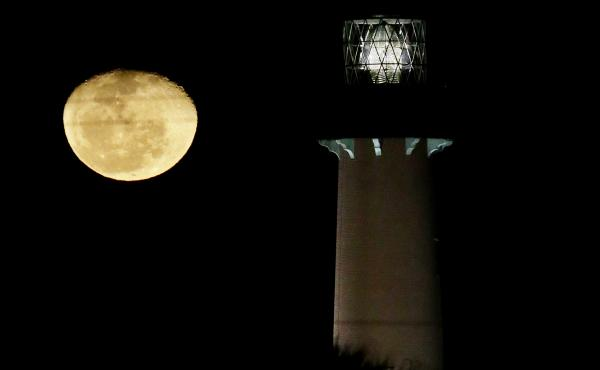 The moon, in its waning gibbous state, rises near the Jupiter Lighthouse in 2013, in Jupiter, Fla. The 108-feet tall, brick structure was first lit in 1860. The lighthouse sits atop a Native American archaeological site, which is at risk from the rising s