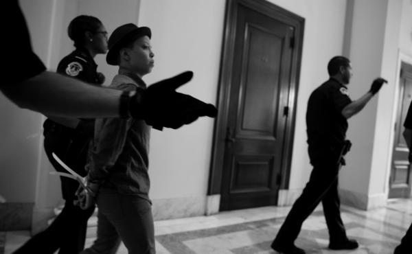 Police officers lead several protesters away from Flake's office Friday after the Senate cloture vote.
