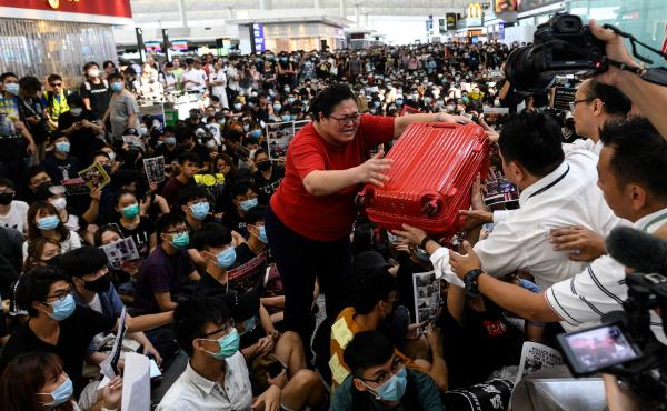 A tourist gives her luggage to security guards as she tries to enter the departures gate during another demonstration by pro-democracy protesters at Hong Kong's international airport on Tuesday.