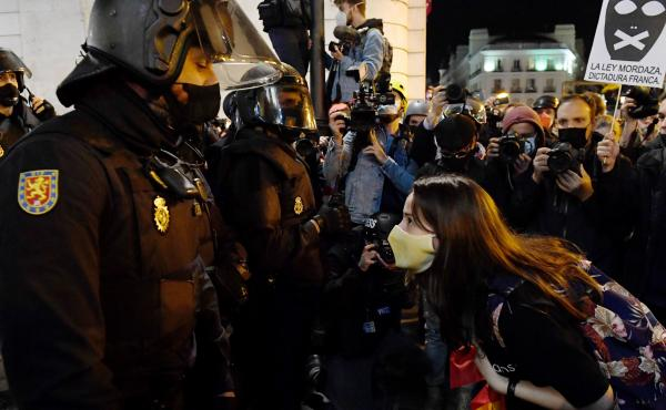 A woman talks to police during a demonstration against the imprisonment of Spanish rapper Pablo Hasél in Madrid. Clashes between police and protestors have gone on for three days and have led to dozens of arrests and injuries.