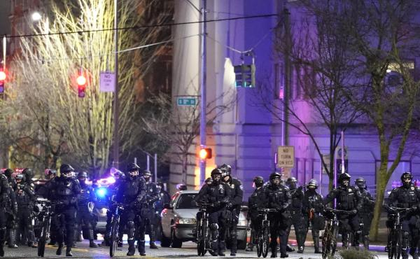 Police and other law enforcement officials stand in a line as protesters approach in the street in front of the City-County Building on Sunday in Tacoma, Wash.