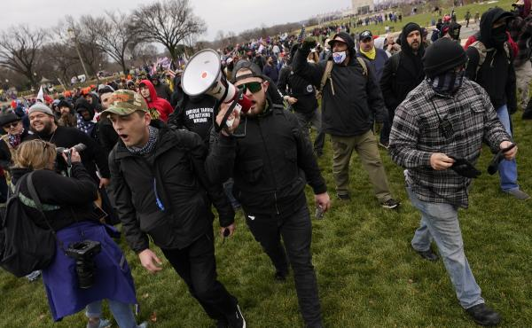 Ethan Nordean, pictured on Jan. 6 with backward baseball hat and bullhorn, leads members of the far-right group Proud Boys in marching before the riot at the U.S. Capitol. Nordean, 30, of Auburn, Washington, has described himself as the sergeant-of-arms o
