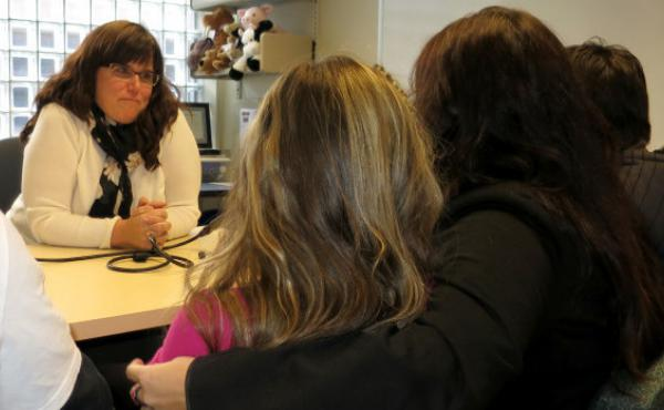 Michaela leans on her mother, Dee, while talking to Dr. Karin Selva about puberty suppression.
