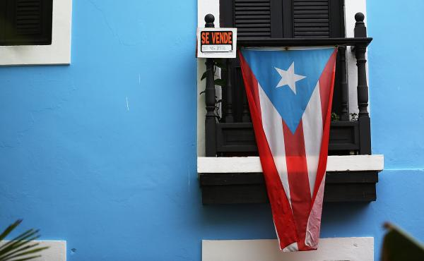A Puerto Rican flag hangs beside a for-sale sign on a balcony in San Juan in summer 2015.
